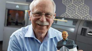 El padre de la impresión tridimensional Chuck Hull posando con su busto impreso en 3D