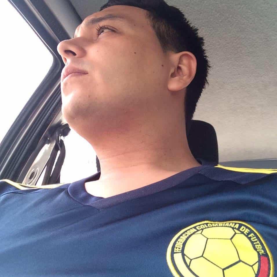 Hombre en auto mirando fuera de la ventana con camiseta de la selección Colombia