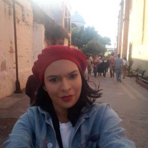 Mujer con gorro rojo paseando en una calle