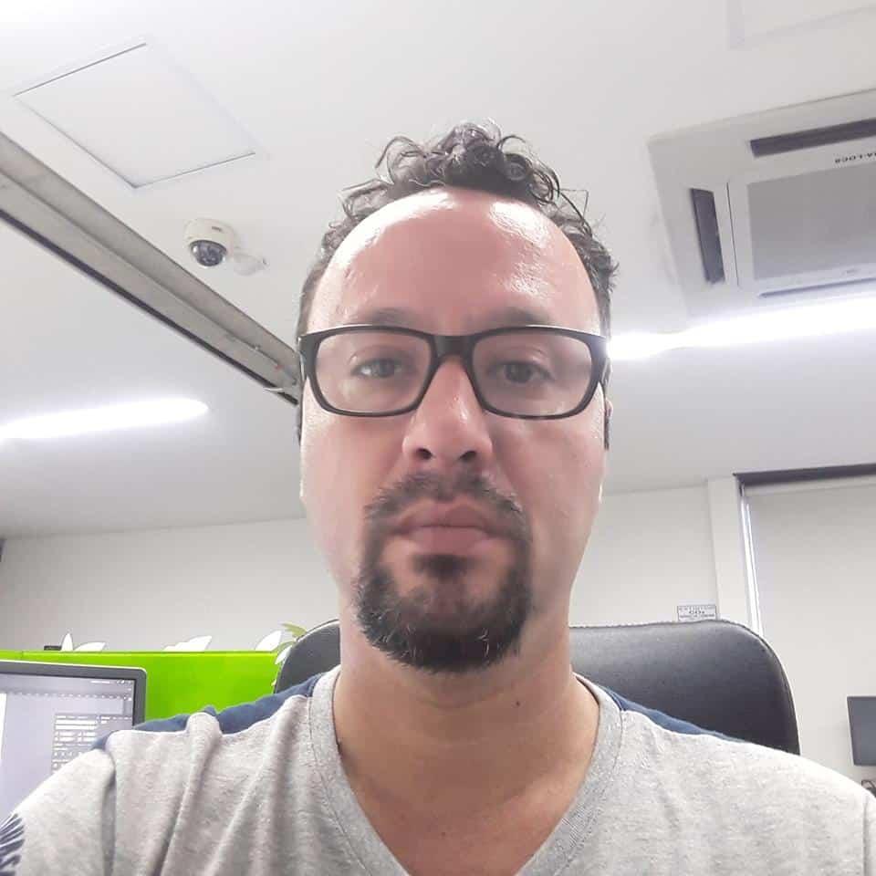 Hombre de mediana edad con gafas y camiseta gris en una oficina